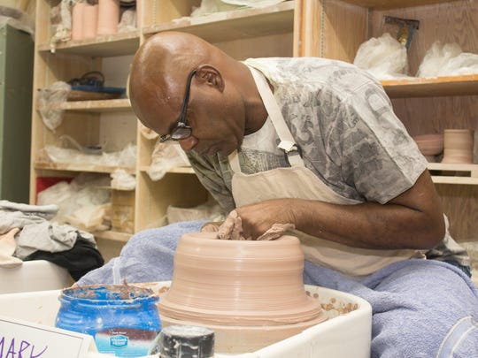 An artist woks on creating a bowl to be sold at the