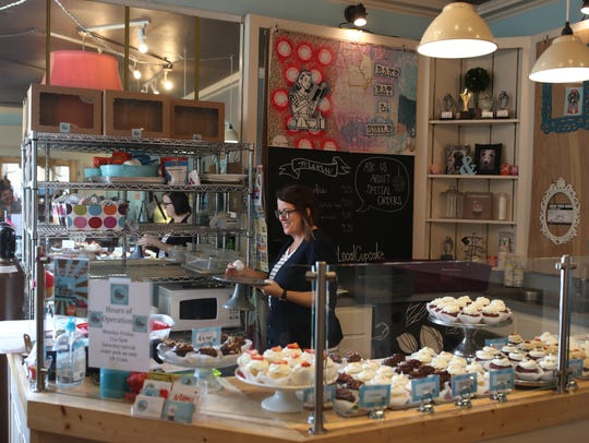 Lucy & Leo's Co-owner Paula Lucas puts out cupcakes