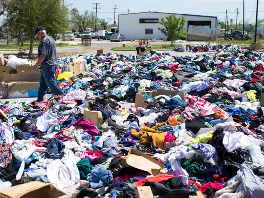 A man walks through clothing in front of Castaways