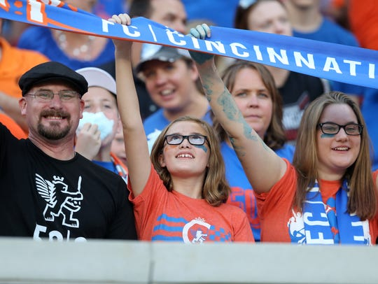 FC Cincinnati fans raise a team scarf before the USL