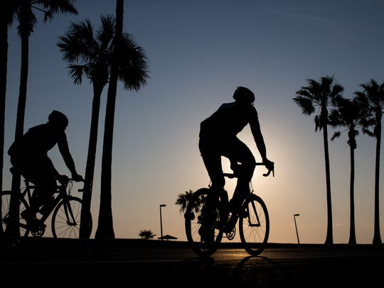 Riders bike on Ocean Drive as they take part in the