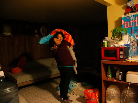 In this file photo, Roselia Sardeneta picks up her 4-year-old daughter as she gets ready to leave for work in the fields on morning.