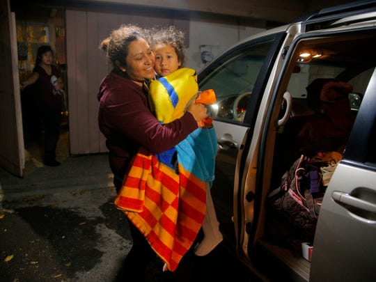 Around 5:30 a.m., Salinas resident Roselia Sardeneta takes her youngest child to the car to drop her off with a babysitter before going to work in the fields. Her other daughter (far left) closes the door behind her and will get ready for school with her sisters.