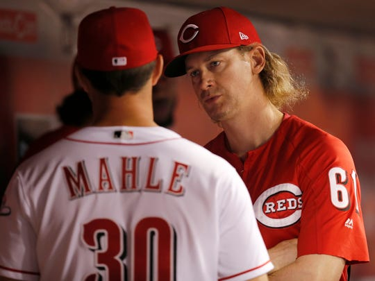 Cincinnati Reds starting pitcher Tyler Mahle (30) talks with starting pitcher Bronson Arroyo (61) in the dugout during the seventh inning of the game between the Cincinnati Reds and the St. Louis Cardinals at Great American Ball Park on Sept. 20, 2017.