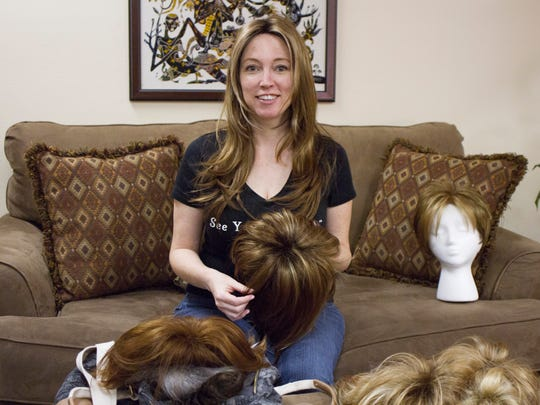 Amber Murray demonstrates the wigs she helps fit to clients Wednesday, Sept. 20, 2017.