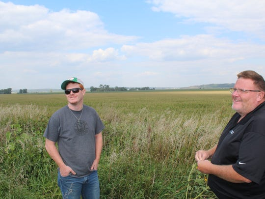 Arthur Wisecup, left, and his father, Lee, will convert a portion of the fields behind them into wetlands. Low-lying areas often flooded out their crops on their farm near Missouri Valley.