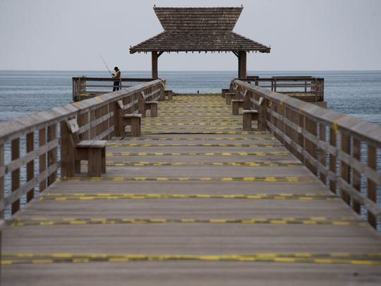 Caution tape lines the second half of the Naples pier Thursday, Sept. 21, 2017, almost two weeks after Hurricane Irma made landfall in Naples. Further assessment of the second half of the pier is required to determine the extent of the damage after a guardrail at the end of the pier blew off in the storm.