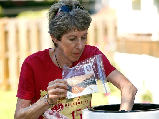 Debbi Hopkins places items into a time capsule before