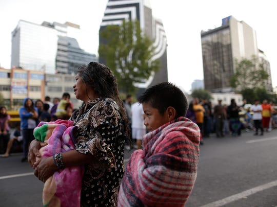 People stand in the street after hearing an earthquake alarm, in Mexico City, Saturday, Sept. 23, 2017. A strong aftershock rolled through Mexico City, Saturday morning, swaying buildings and sending some people running into the street.