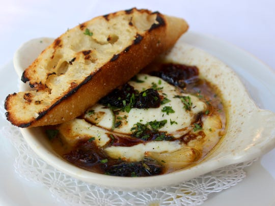 The baked mozzarella, served in a small bowl featuring grass-fed buffalo mozzarella combined with rosemary oil, sun-dried tomatoes, roasted garlic and balsamic syrup, is accompanied with bread.
