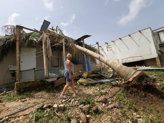 Nelida Trinidad walks around her destroyed home in