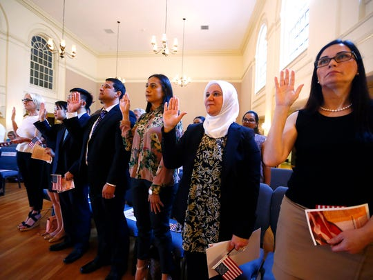 Twenty three new citizens from 13 countries raise their