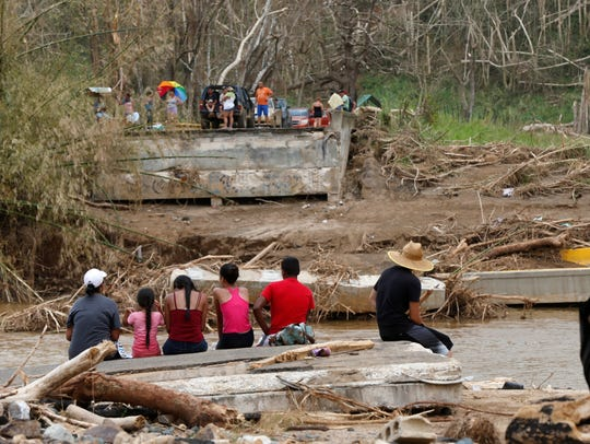 People sit on both sides of a destroyed bridge that