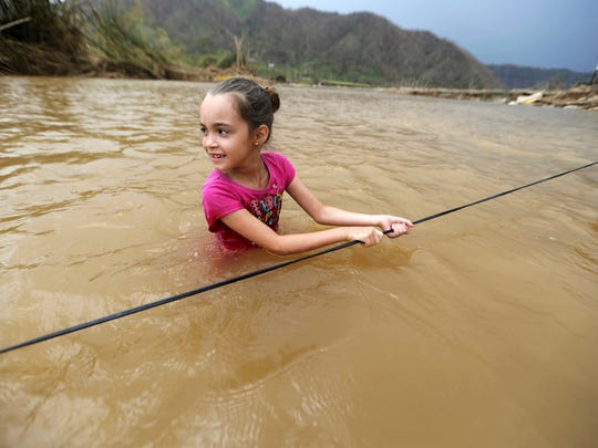 Ruby Rodriguez, 8, looks back at her mother Wednesday as she wades across the San Lorenzo Morovis river with her family, since the bridge was swept away by Hurricane Maria, in Morovis, Puerto Rico.