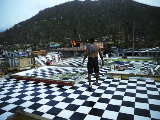 In this Tuesday, Sept. 26, 2017, file photo, Nestor Serrano walks on the upstairs floor of his home, where the walls were blown off, in the aftermath of Hurricane Maria, in Yabucoa, Puerto Rico. Maria has thrown Puerto Rico's already messy economic recovery plans into disarray. (AP Photo/Gerald Herbert, File)