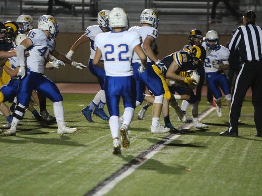 Daniel Carter of Marquette (29) squeezes through the Germantown defense for one of his four touchdowns Sept. 29.