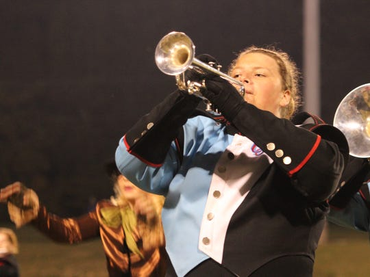 Jason Mosley plays his trumpet while marching with the band at half-time.