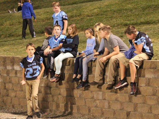 Little League football players and their friends watch the game from the sidelines.