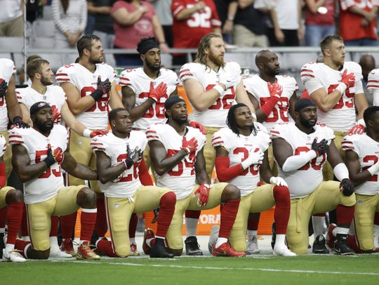 San Francisco 49ers kneel during the national anthem
