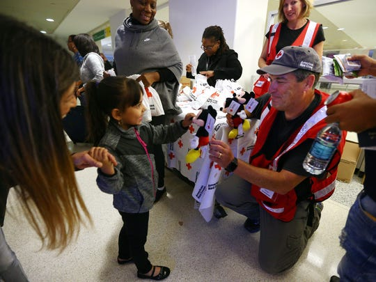 A Red Cross volunteer gives a Mickey Mouse doll to