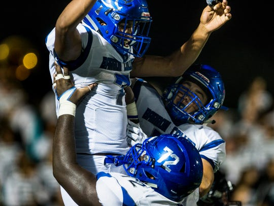 Barron Collier's Jayden Rolle, #7, gets lifted by teammates