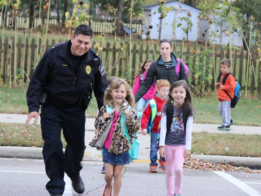 Eagle-Police-Chief-Gregg-Duran-leads-Kennedy-Basterash-and-Carly-Callan-and-over-the-crosswalk-.JPG