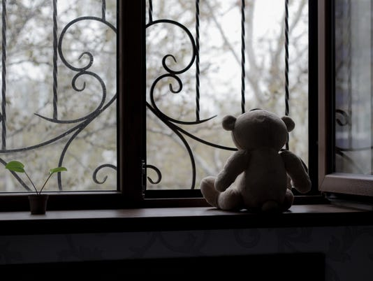 Teddy bear staring out window