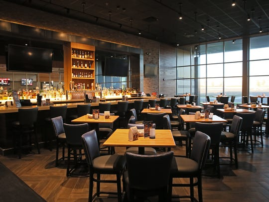 The lounge and dining room at BistroPlex have seating at tables, booths and the bar.