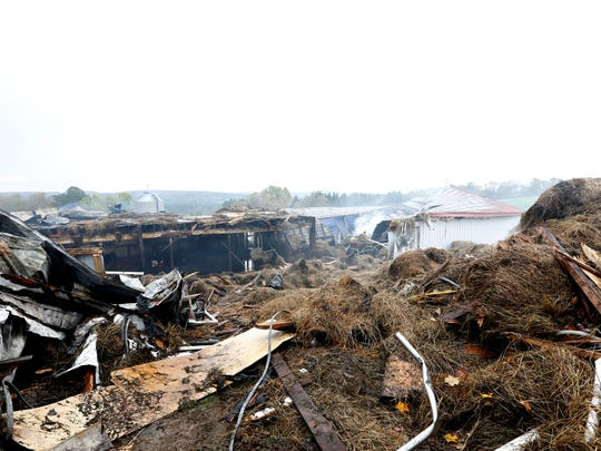 Smoldering hay bales and debris outside the dairy barn at Aukema Dairy Farm in Chenango Forks on Wednesday October 11, 2017. A fire destroyed a barn at Aukema Dairy Farm on Oct. 10.