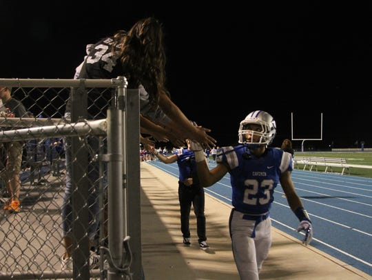 Senior Evan Lara gives high-five to students following