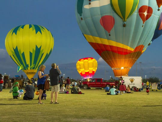 Spectators watch the balloons at the Salt River Fields