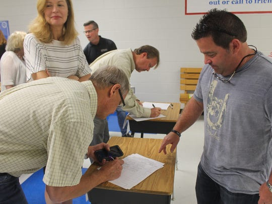 Powdersville resident Tim Mahoney signs a petition seeking a referendum on zoning regulations.
