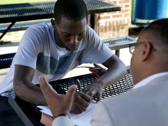 Brian King fills out a survey for the city's developing TEMPO program at Sunrise Place Apartments. King, a father of two, wants to get his GED so that he can apply for college.