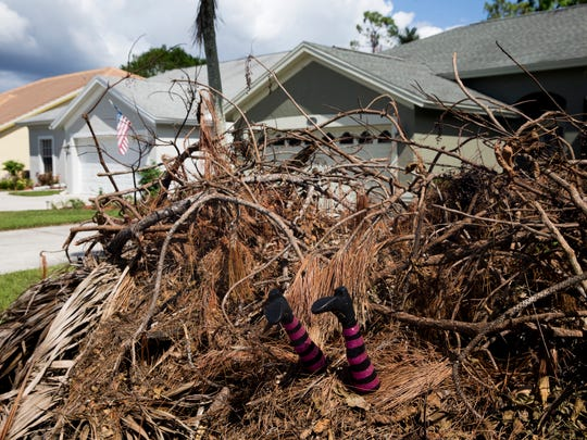 """""""At least she killed the Wicked Witch of the Southwest,"""" joked Kathleen Waido in reference to Hurricane Irma and the buried witch legs in her front yard. """"I think it's just cheering people up. We can't move these piles."""" Mounds of debris, leftovers from Hurricane Irma over a month ago, litter the Berkshire Lakes neighborhood Thursday, Oct. 19, 2017, in East Naples. With Halloween only a week away how will trick-or-treating be affected by the nuisance, if at all?"""