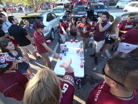 A group of students plays beer pong outside of Doak Campbell Stadium. Festivities have quieted down outside the stadium as the Seminoles' record has brought more early games to town this season.