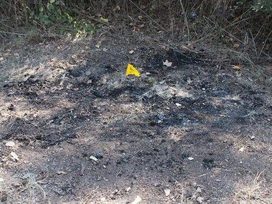 An evidence flag remained at the scene where two bodies