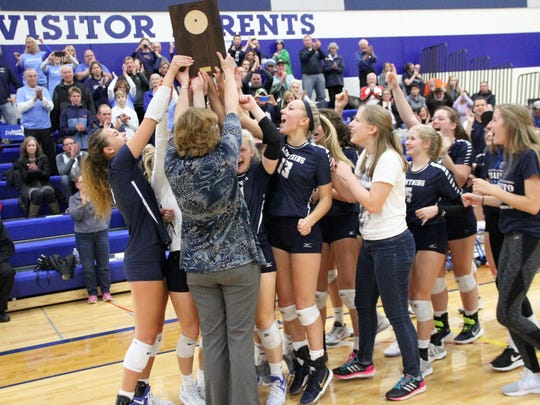 Lake Country Lutheran coach Janet Bahr hoists the sectional championship plaque Oct. 28.