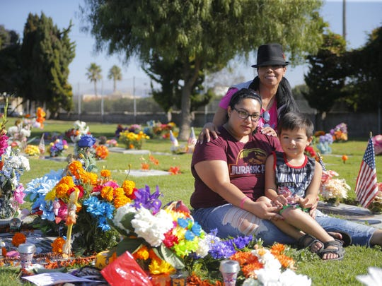 Isabel Estrada, Maria Estrada and Anthony Guzman visiting their loved one at Garden of Memories.