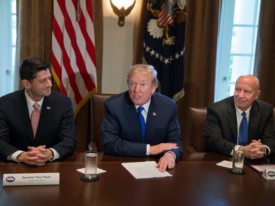 President Trump sits between Speaker Paul Ryan and