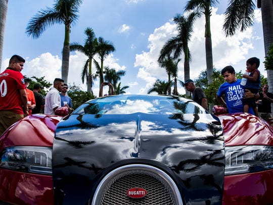 People check out the 2012 Bugatti Veyron Grand Sport