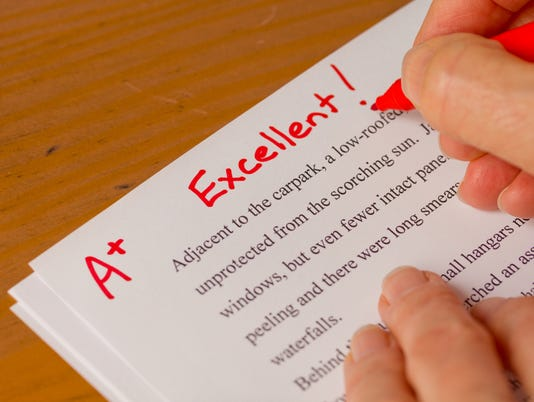 Hand and Red Pen Grading Papers with Excellent