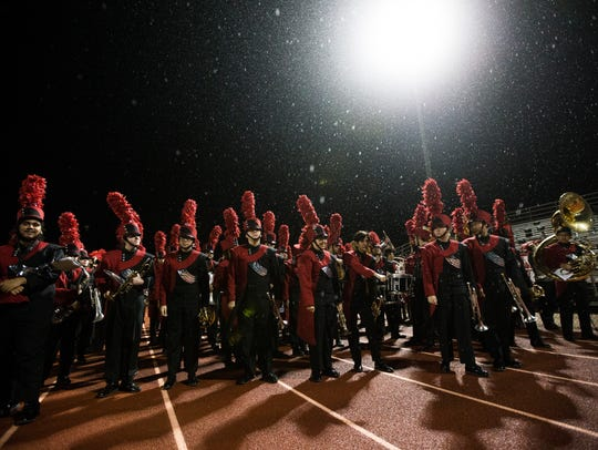 Ray's band waits in the rain during the District 30-5A