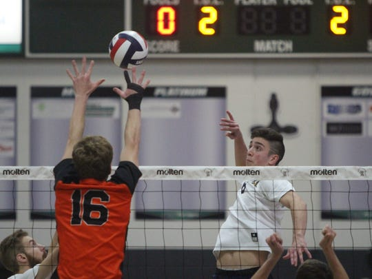 David Kopriva takes a swing for Marquette with Kaukauna's Ben Brochtrup rising to block in the WIAA boys volleyball state championship game Nov. 11.