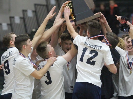 Marquette players celebrate with the trophy after winning the WIAA boys volleyball state championship Nov. 11, 2017 at Wisconsin Lutheran College.