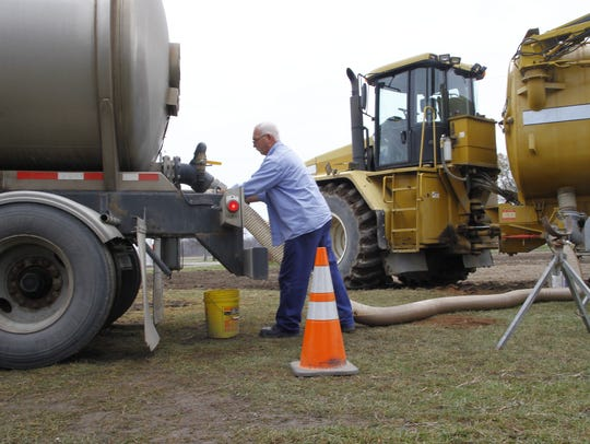 Dennis Harshman hooks up a hose to the back of a tanker