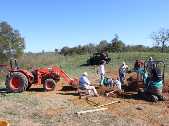 Mark LeMay (on tractor) uncovers the grave of Tidence Lane from a family cemetery in Morristown, as volunteers helping with the dig look on. The remains of Lane and other family members were moved to First Baptist Church, Whitesburg.
