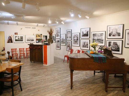 An exhibition of photographs and a baby grand piano