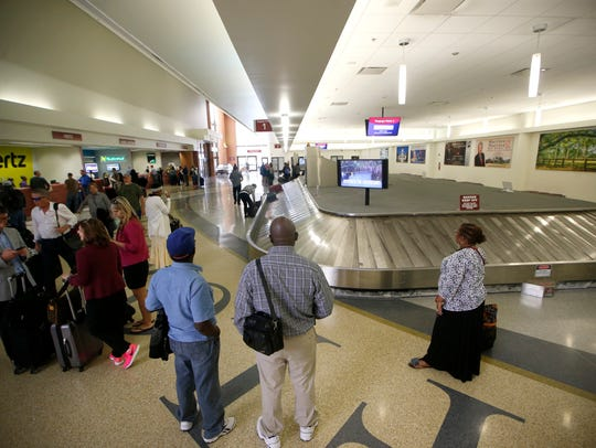 Passengers wait at the baggage claim at Tallahassee