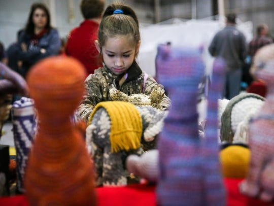 Savanna Smith, 5, looks through crocheted dolled during