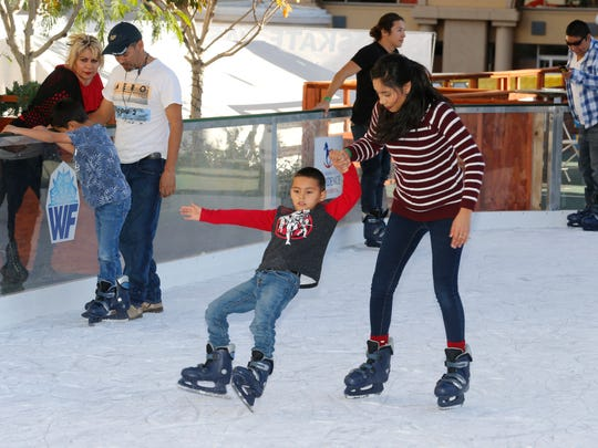 A young skater gets a helping hand Saturday at WinterFest in Downtown El Paso.